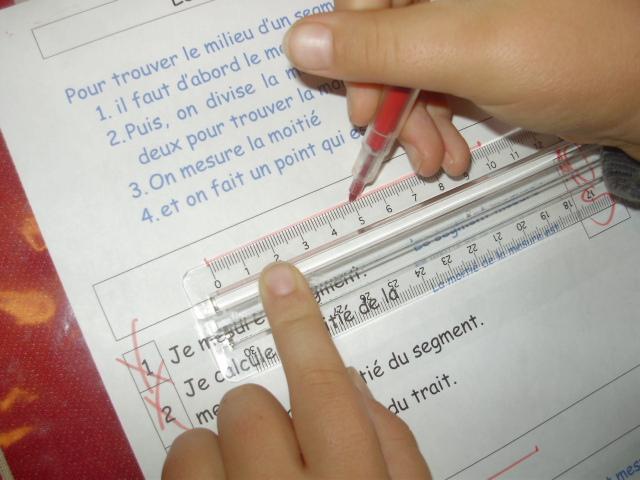 L enfant mesure la moitié avec la règle et fait un petit repère sur le  segment. b58120daaf31